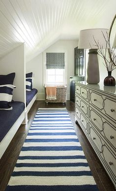 Cottage attic kids' room features a beadboard ceiling over built-in twin beds dressed in white and navy blue stripe shams and blue blankets situated across from a Bernhardt Cabrillo Nailhead Dresser across from a white and navy stripe runner placed in front if a woven hamper on wheels under window beside a black dutch door.