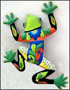 """Green Frog Patio Art - Painted Metal Wall Décor - 18"""" x 24"""" . $39.95. Hand painted metal frog wall hanging. Can be used both indoors and outdoors. The frog is hand cut from recycled steel drum. The details of the design have been hammered into a bas-relief to accent the painted decorative designs. The choice of rich colors is especially attractive. The painting style is similar to that found on Spanish & Mexican talavera pottery."""