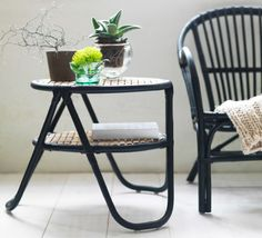 A side table in black rattan with natural bamboo table top, shown together with a black rattan armchair.