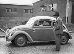 """Ferdinand Porsche observes one of the 1937 Type 30 (""""V30"""") test vehicles. With this model, the true Kdf-Wagen (the future Volkswagen) has taken shape, with fender mounted headlights. The trunk lid is much smaller than in the eventual production version."""