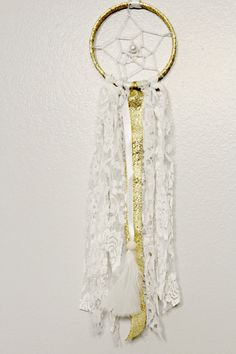 Small Dreamcatcher in Gold and White  Measures 3 across hoop by 13 long (not including ribbon hanger)  The hoop is wrapped in shiny gold ribbon and