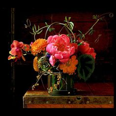 Peonies, dahlias, and orchids in a leather-strap vase