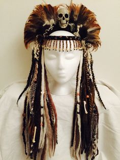 This Voodoo Priestess Headdress is crowned with a spooky skull nestled in a bed of reddish brown rooster feathers. Many hanging white, brown, and