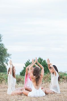 Boho women meditating with hands clasped overhead in circle in rural field