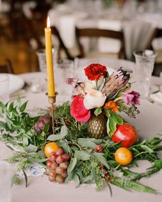 Tables from Essential Details were covered in white tableclothsand topped with fruit (grapes, oranges, and more),brass candles,and floral centerpieces from Jaclyn Journey.