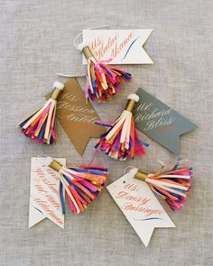 Paper tassels created by Parcel, a vendor whose goods are sold in Fiona's store, hung from each calligraphed escort card.