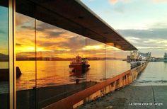 El barco que llega de Somo, se refleja en el embarcadero de Santander.