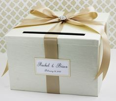 """Wedding Card Money Holder Box Ivory and Champagne Customizable. This Card Box is big enough to hold around 200 cards. The slot is big enough for those unusually shaped cards. You can be assured that the cards, gift cards and money inside are secure and not easy to open. Customize your Card Box by selecting your choice of Box Fabric Color and Ribbon Color. Personalized by adding the Name Tag to your Card Box. Card Box measures: 11x11x7"""" We hand make with care using only the finest…"""