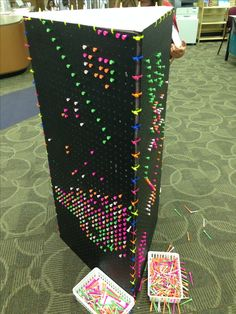 Neon golf tees in peg board panels tied together with zip ties- big makeshift Lite Brite that more than one person can use @ a time to create individual designs