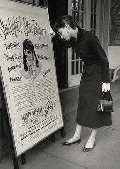 "Audrey Hepburn reading the Broadway poster for ""Gigi"""