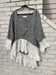 This is the Thea Tunic. Youll love having this dreamy ruffled creation in your upcycled wardrobe. The flannel is cozy warm and the repurposed ruffles give it a romantic flair. The flannel has a tiny Herringbone check of green, purple and cream that from a distance looks dark green. I