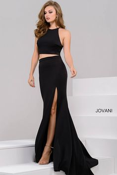 Sexy floor length form fitting two piece black jersey prom dress with high slit features sleeveless bodice with high neckline.