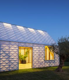 Hand cut polycarbonate shingles cover a gabled roof and walls. Photo by: Tim Van de Velde