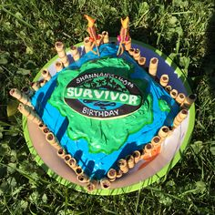 Homemade Survivor cake by @passion4film - Pirhouette cookie bamboo border, tiki torch candle accouterments, icing island and centerpiece cookie by @dascookie
