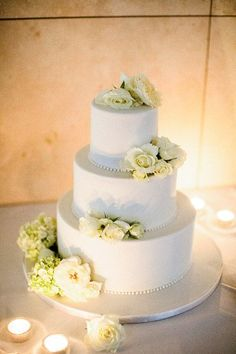 A classic three-tier wedding cake decorated with white buttercream icing and fresh white David Austin roses, by Cake Ink. Photography by Adrian Tuazon Photography.