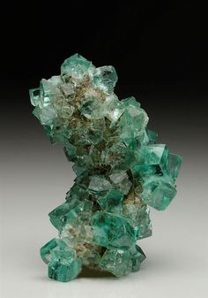 Gemmy well formed twinned crystals of light green Fluorite almost completely cover an alter Limestone matrix with a single cubooctahedral Galena crystal from Height's Mine, Weardale, Co. Durham.