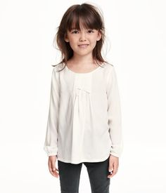 Long-sleeved blouse in airy woven fabric. Decorative pin-tucks and bow at front, buttons at back of neck, and elasticized cuffs.