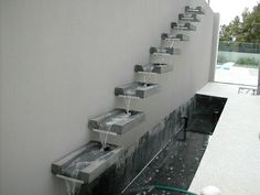 Overflowing granite spouts water feature cantilevering from wall
