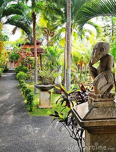 A photograph showing the layout of a beautiful resort garden and path way in Ubud, Bali.  With open style pavilion or local pavilion called bale in the garden surrounded by lush natural tropical landscaping, and antique stone decor sculpture.  Vertical color image, nobody in picture.  Travel photography with ethnic art and architecture interest.  Bali tourism.