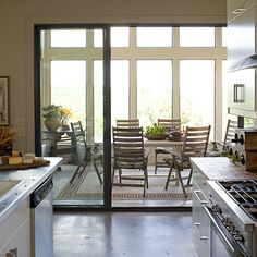 Dining Porch:  A 12-foot wall of sliding glass doors opens up the entire kitchen to the dining porch. The spacious screened dining porch makes eating every meal outside a reality.  Concrete floors throughout the kitchen and dining porch add to the indoor/outdoor feel.