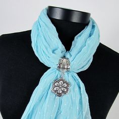 "The flower pendant scarf jewelry has a light hammered metal finish bordered in a swirl design inset with black. This scarf jewelry item easily slides on to many scarves adding a ""charming"" touch. Scarf not included."