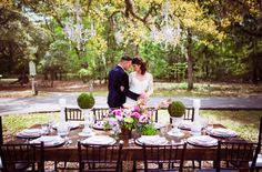 Bride and groom at their forest wedding tablescape with chandeliers hanging on a tree