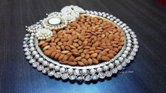 Description - Crystal Pearl Tray with a tee light Size - fits in quarter to half kg of goodies Colors - White pearls & crystals Price on request For orders/ inquiries/ bulk/ prices call me on 8976921339 or drop me an email on wrapp.a.smile@gmail.com