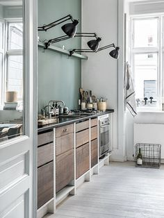 Scandinavian kitchen with a green contrast wall, wood cabinents and black wall sconces