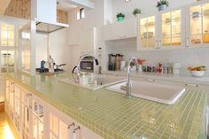 タイル壁と壁・収納家具の色を揃えたことでスッキリした印象に。キッチンの天板はグリーン系を持ってくることでアクセントにしています。