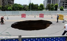 July 2012:This huge sinkhole suddenly appeared on a main road in Changsha, capital of southern China's Hunan Province. The enormous hole opened up at around 1am and swallowed up a car - killing one and injuring a further three people.