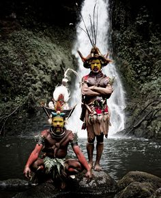"""Huli Tribe, PNG.  Papua New Guinean tribes fought """"over land, pigs and women. Great effort is made to impress the enemy. The largest tribe, the Huli wigmen, paint their faces yellow, red and white and are famous for their tradition of making ornamented wigs from their own hair. An axe with a claw completes the intimidating effect."""" - Before They Pass Away"""