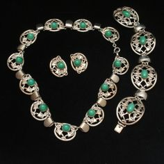 Exceptional, ornate parure in silver tone metal that resembles sterling. In fact, I was surprised to find it wasn't silver when I tested it. The necklace has domed green glass cabs and spring ring cla