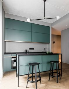 Lithuanian interior design studio AKTA used flat-front cabinets, dramatic bold accents and a unique aqua green color in this modern kitchen. | Photographer: Leonas Garbačauskas