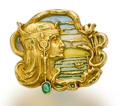 An art nouveau eighteen karat gold, enamel and emerald brooch, Joe Descomps, circa 1900  designed as a maiden in profile, with a blue, yellow and green plique-à-jour enamel background and oval-shaped emerald detail; signed J. Descomps; width: 1 1/4in.