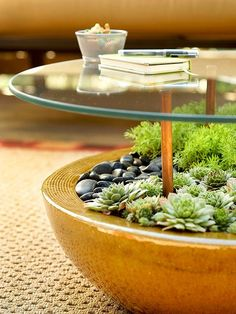 """Structure a nifty table by sinking rubber-tipped copper pipe into a large, rock-filled planter holding succulents or plants that don't need a lot of water. Place at least four of the pipes at equal distances apart within the planter. Use weatherproof adhesive that works with glass and metal to secure a glass tabletop to the rubber pipes."""