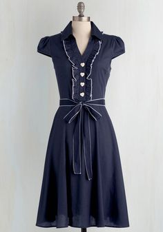 This delightful navy shirtdress grew up dreaming about one day becoming a fashion icon. Today, it's on its way with dapper ruffles, heart-shaped buttons and precise white trim to round out its repertoire. Check out this dashing design in a host of other haute hues!