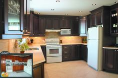 Rénovation d'une cuisine contrastante- Rénovation d'une cuisine incluant des armoires et moulures de bois ainsi que la pose de céramiques au sol et au dado. Le comptoir est de quartz. Le mur séparant la cuisine de la salle à manger a été enlevé lors de la rénovation de cette cuisine.