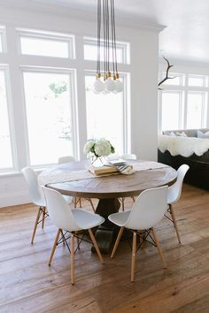 Eat-in kitchen boasts a Schoolhouse Electric Brass City Chandelier 7 illuminates a round salvaged wood dining table lined with Eames Molded Plastic Chairs.