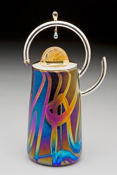 """Briolette Teapot  Blown, iridized glass vessel with fabricated sterling silver lid, handle and spout. Rutilated quartz, amethyst, topaz, and aquamarine set in 22 karat gold adorn the silver. 7"""" tall"""