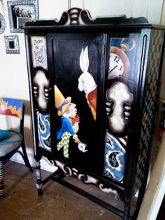 "À tall cabinet painted with an ""Alice in Wonderland"" theme."