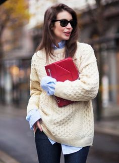 cozy knit sweater layered over a long button-up and paired with a red clutch