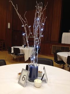 Centerpieces for my wedding. Navy, silver and white. I bought vases at JoAnn's and filled them with colored sand. You can get it the cheapest at fish stores like PetCo. Then I put 3 silver branches in the vases. I also used 2 battery powered LED light strands. They were turned on and paired with the escort cups to make my tables glow. Each centerpiece was surrounded by 3 bowls with nuts and mints. 3 silver frames - the table number, a thank you from bride and groom, & info about the photo…