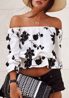 Beauty model wearing embroidered floral off-shoulder top with handbag