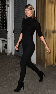 Taylor Swift wears a fitted black turtleneck, skinny jeans, and black boots
