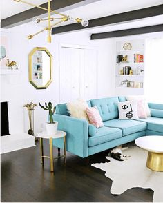 living room with turquoise sectional sofa, mid-century modern interior, pantone island paradise, light turquoise, sky blue, baby blue, caribbean blue, aqua blue, tiffany blue, gold accents, dark wood floor, dark wood beams