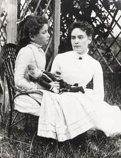 "The photo was taken in Brewster, Cape Cod, Massachusetts and shows eight-year-old Helen Keller hand in hand with her teacher Anne Sullivan. Both Keller and Sullivan indicated later in their journals that ""doll"" was the first word Helen Keller learned in sign language in March 1887"