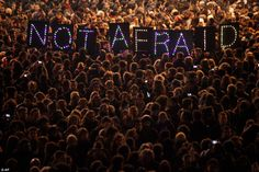 Standing in support of the freedom of the press, these protesters hold an illuminated sign at a gathering in the center of Paris, January 2015.