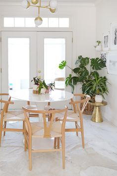 Elsie's Spring Room Refresh // Plant filled home. Lovely dining nook with white tulip table, light wood wishbone chairs, brass accents and lighting.