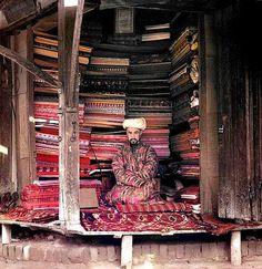 Venditore di tessuti a Samarcanda, inizio del sec. XX. Indossa una veste chapan di seta tinta in batik. Grazie Musée Guimet e Giovanni Carboni (foto di Sergueï Prokoudine-Gorski [domaine public])