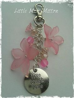 A gorgeous bag charm/key ring. It has various pretty pink glass beads, acrylic pink flowers and a silver plated live, laugh, love disc Ready to post via royal mail 2nd class post x